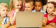 Jeunes enfants qui regardent un ordinateur portable avec attention